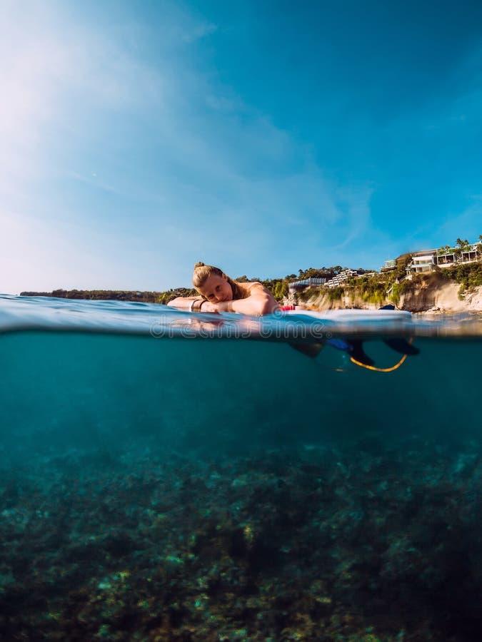 Surfarekvinna att koppla av med surfingbrädan och den väntande vågen Bränningflicka i havet royaltyfri bild