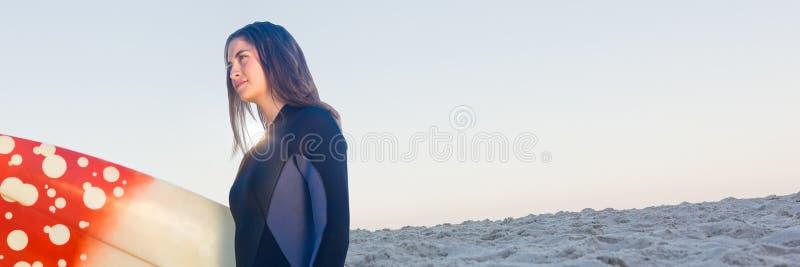 Surfarekvinna som ser till vänstert mot den sommarhimmel och stranden royaltyfri bild