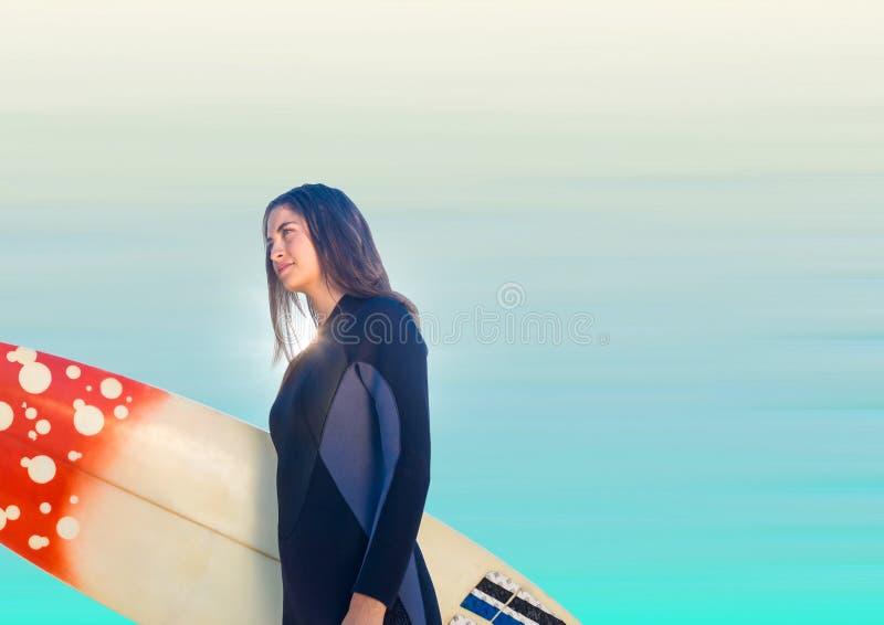 Surfarekvinna som ser till vänstert mot oskarp blå bakgrund royaltyfri fotografi