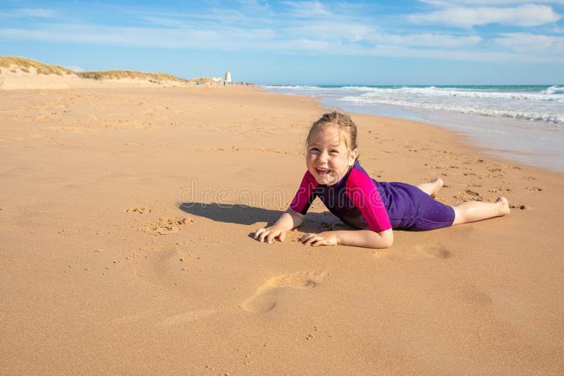 Surfareliten flicka som ligger på sand av stranden och ser le fotografering för bildbyråer