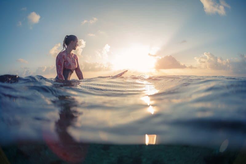Surfaren för den unga damen väntar vågorna royaltyfri bild