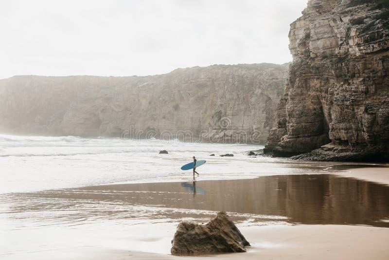 Surfaren går in i vattnet för att surfa royaltyfri bild