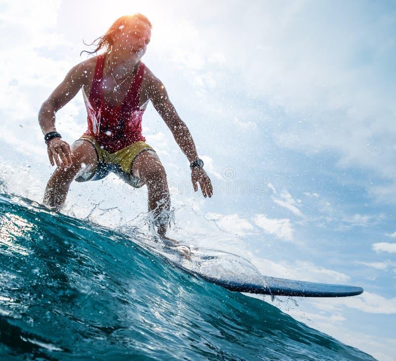 Surfaren rider vågen arkivfoto