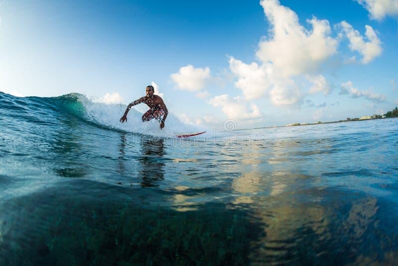 Surfaren rider vågen arkivfoton