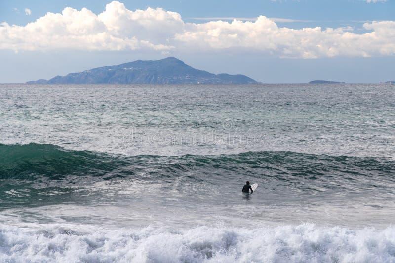 Surfaren tar en våg, på en surfingbräda, glidbanor längs vågen, i bakgrunden av berget, Sorrento Italien arkivfoto