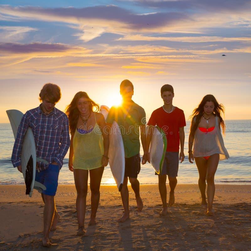 Surfarepojkar och flickor grupperar att gå på stranden arkivbilder