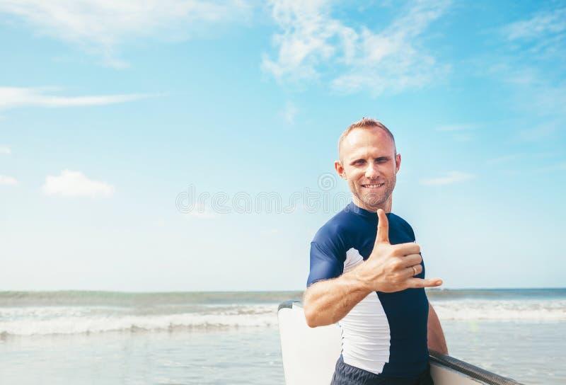 Surfarestående för ung man som in camera visar surfares berömd gest för Shaka tecken när honom som kommer med det långa bränningb royaltyfri foto