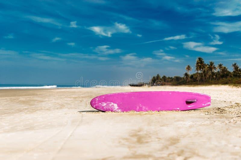 Surfboard на тропическом пляже обозревая океан, предпосылку голубого неба Покрашенная доска для серфинга на песке стоковые изображения rf