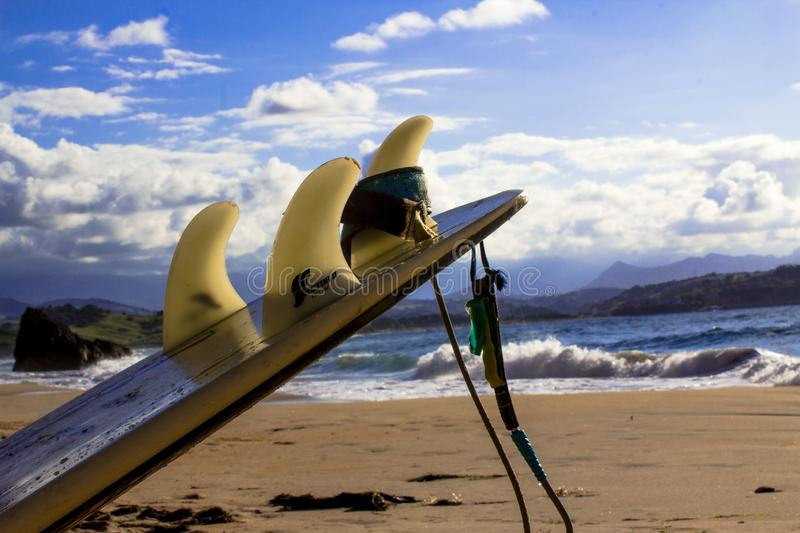 Surfboard with fins and leash on a beach at the ocean in spain royalty free stock image