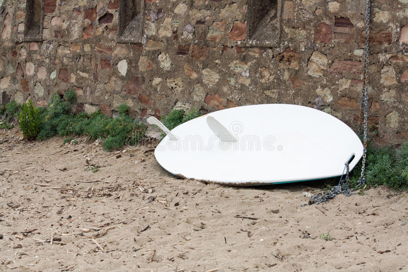 Surfboard leaning against the wall. An unused Surfboard leaning against the wall stock photography