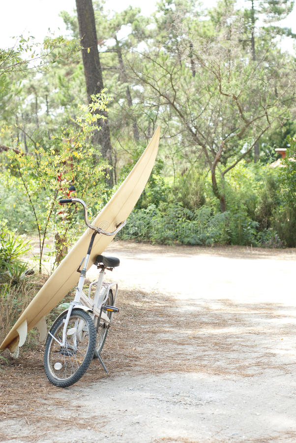 Surfboard leaning against white bike. Bike and surfboard parked at side of road near beach stock photo