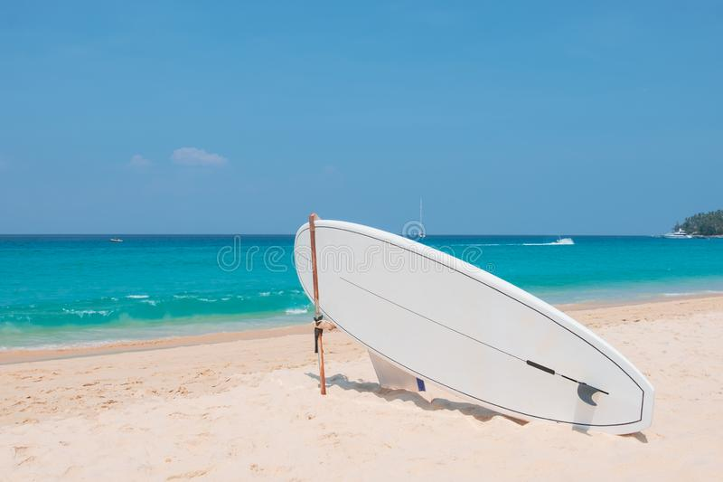Surfboard on tropical beach with blue sea in summer. royalty free stock photography