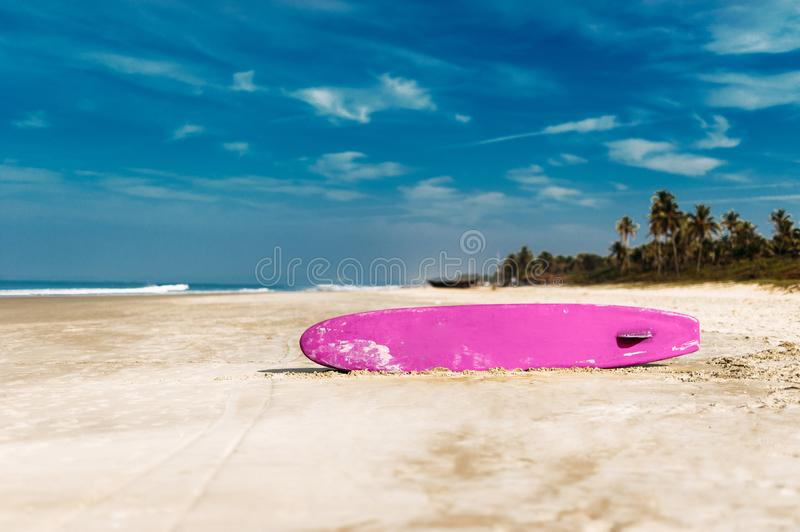 Surfboard on a tropical beach overlooking the ocean, blue sky background. Colored Board for surfing on the sand royalty free stock images