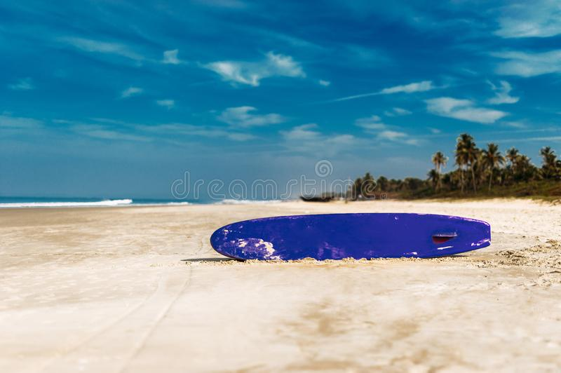 Surfboard on a tropical beach overlooking the ocean, blue sky background. Colored Board for surfing on the sand royalty free stock photography