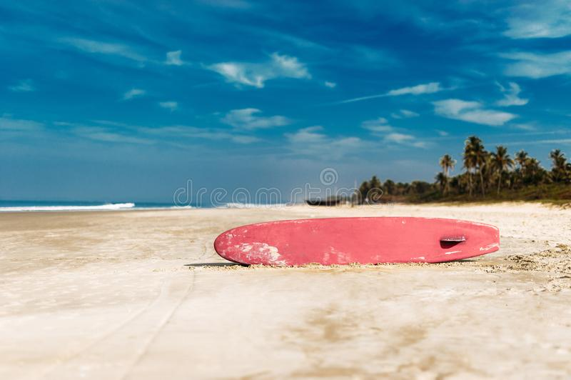 Surfboard on a tropical beach overlooking the ocean, blue sky background. Colored Board for surfing on the sand stock image