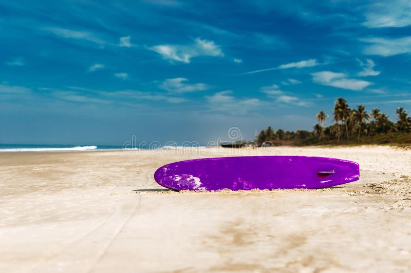 Surfboard on a tropical beach overlooking the ocean, blue sky background. Colored Board for surfing on the sand stock photo