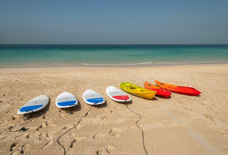 Surfboards и каяки на песчаном пляже стоковые изображения