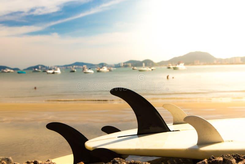 Surfboards лежа на утесах морем с большой группой в составе яхты причаленные на заднем плане стоковое изображение