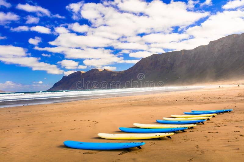 Surfboards на широком песчаном пляже Famara - известном пляже для серфинга стоковые изображения