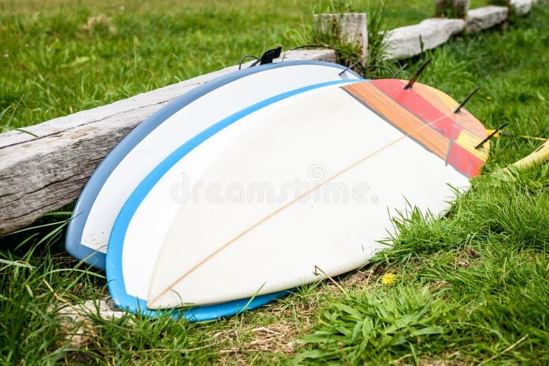 Surfboards штабелированные и положенные против деревянной загородки кладя на gro стоковое фото