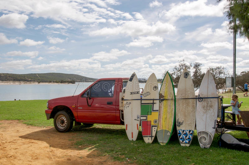 Surfboards for Hire. KALBARRI,WA,AUSTRALIA-APRIL 18,2016: Red truck with surfboards for hire on the foreshore of the Murchison River with tourists in Kalbarri stock images