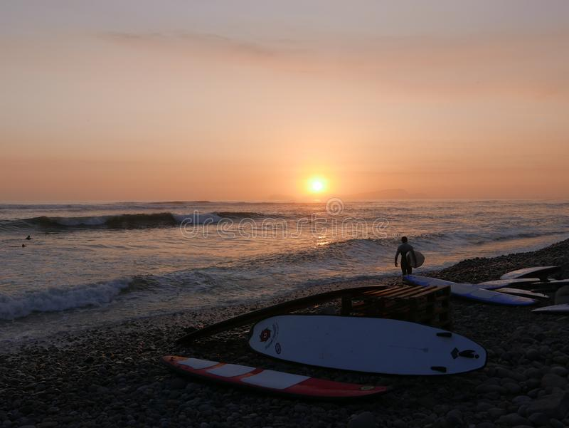 Surfboards and yellow and red sunset in Lima stock photo
