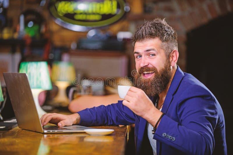 Surfend Internet Zit de mensen gebaarde zakenman bar met laptop en kop van koffie Freelance voordeel Online manager het werk royalty-vrije stock fotografie