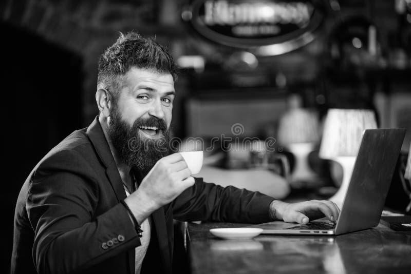 Surfend Internet Zit de mensen gebaarde zakenman bar met laptop en kop van koffie Freelance voordeel Online manager het werk royalty-vrije stock foto's