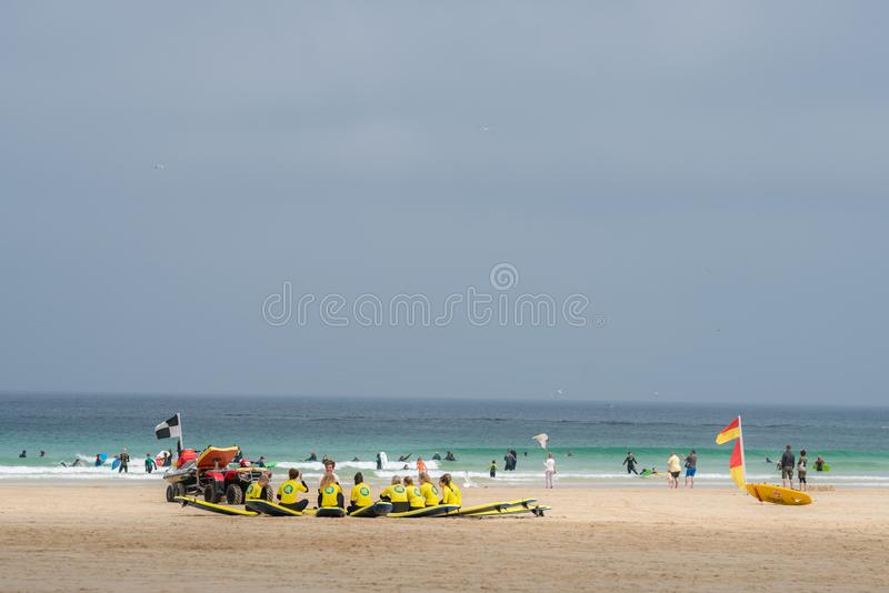 Surfende Schulsitzung auf einem Strand stockfotografie
