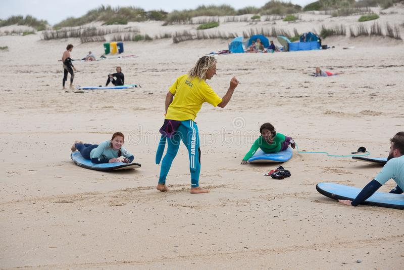 Surfender Trainer weist Anfängersurfer auf dem Strand an stockbilder
