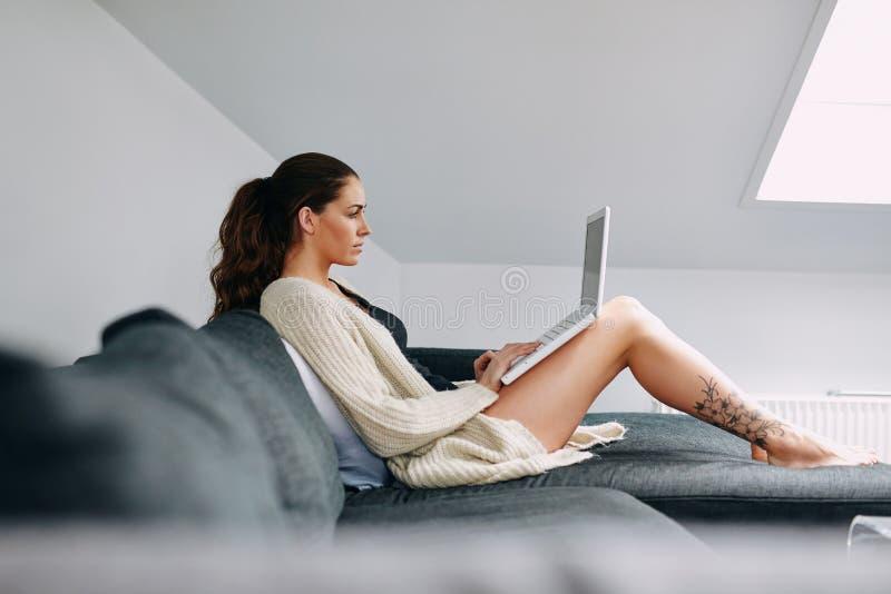 Surfendes Internet des attraktiven Brunette auf Laptop lizenzfreie stockfotografie