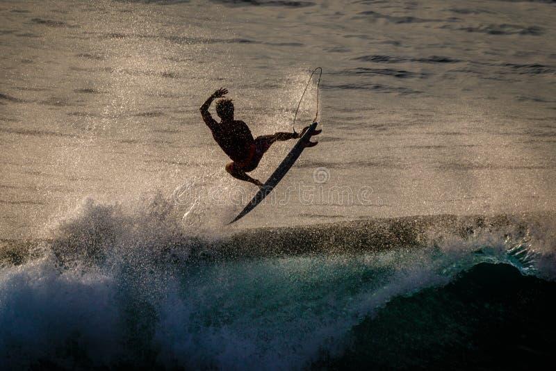 Surfer που κάνει την αντιστροφή αέρα σε Uluwatu στο ηλιοβασίλεμα ακραίος αθλητισμός lifestyle Μπαλί Ινδονησία στοκ εικόνες