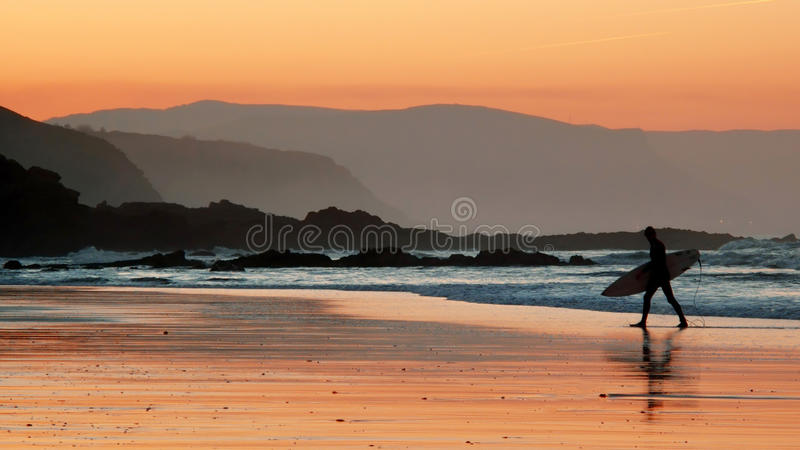 Surfer στην παραλία στο ηλιοβασίλεμα στοκ εικόνα με δικαίωμα ελεύθερης χρήσης