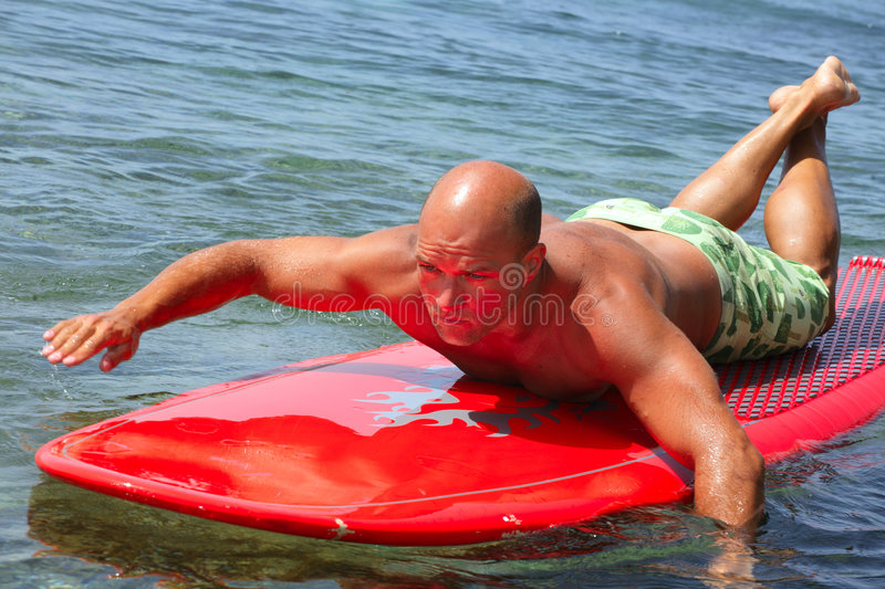Surfer. Tan surfer on a paddling board royalty free stock photography