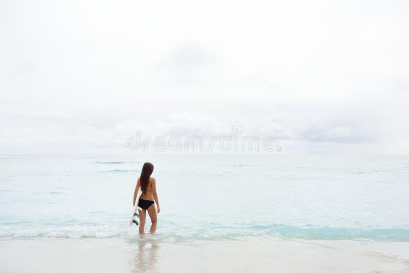 Surfer allant de fille de surfer regardant la plage d'océan photographie stock libre de droits