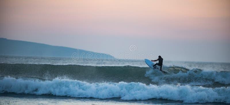 Surfer attrapant une vague au coucher du soleil image stock