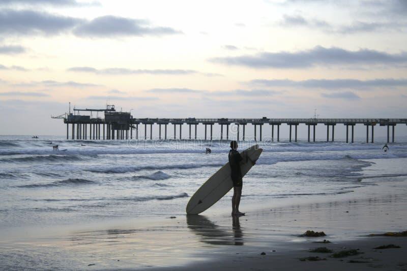Surfer au crépuscule devant le pilier de Scripps à La Jolla, la Californie images libres de droits