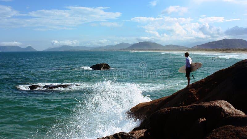 Surfer auf den Felsen in Joaquina-Strand, Florianopolis, Brasilien lizenzfreies stockfoto