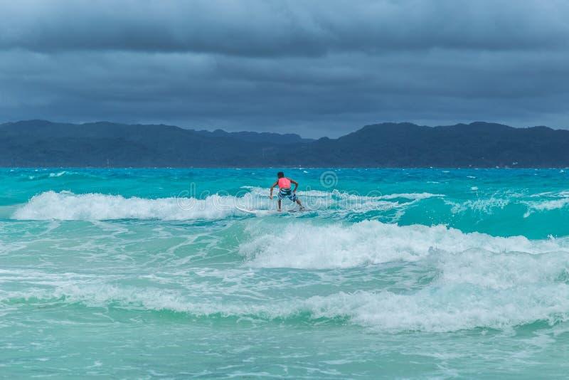 Surfer auf Türkis azurblauem Meereswogen in Siargao, Philippinen lizenzfreie stockfotos