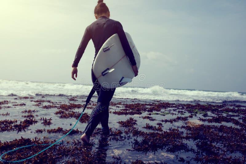 surfer avec la planche de surf marchant sur le récif de bord de la mer images libres de droits