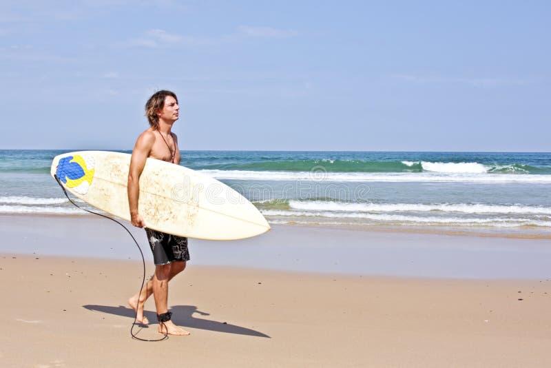 Surfer avec sa planche de surfing à la plage images libres de droits