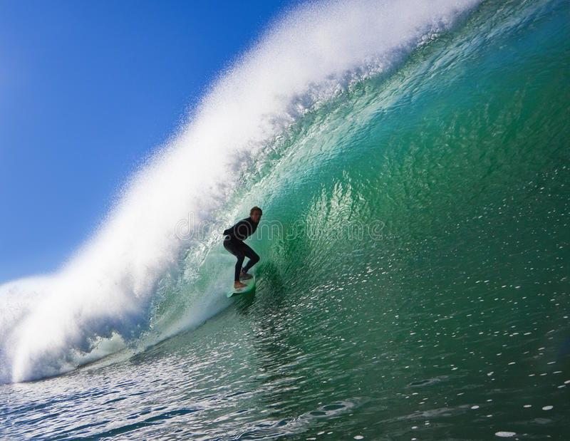 Surfer in the Barrel. Surfer Riding a Perfect Blue wave Getting Epic Barrel stock photo