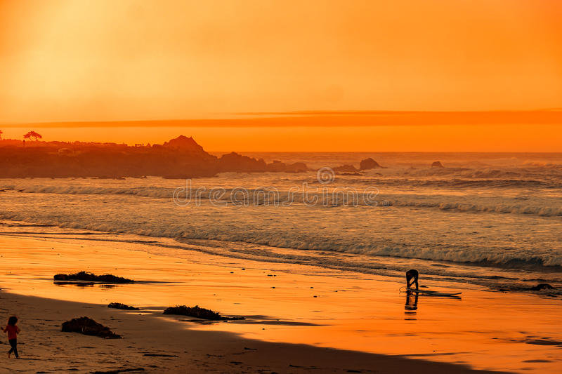 Surfer on beach at Carmel-by-the-Sea stock photography