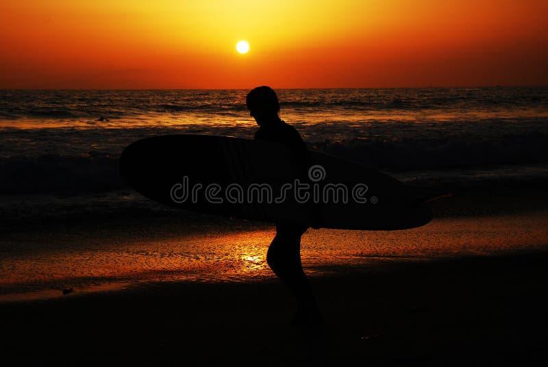 Surfer bei Sonnenaufgang lizenzfreie stockbilder
