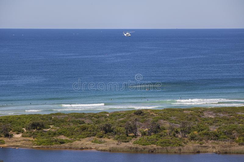 Rescue Helicopter on flying mission over ocean beach royalty free stock images
