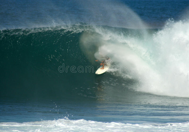 Surfer in a big barrel on the North Shore, Hawaii. Photograph of a surfer catching a big barrelling wave at Backdoor break on the North Shore of Oahu, Hawaii stock photography