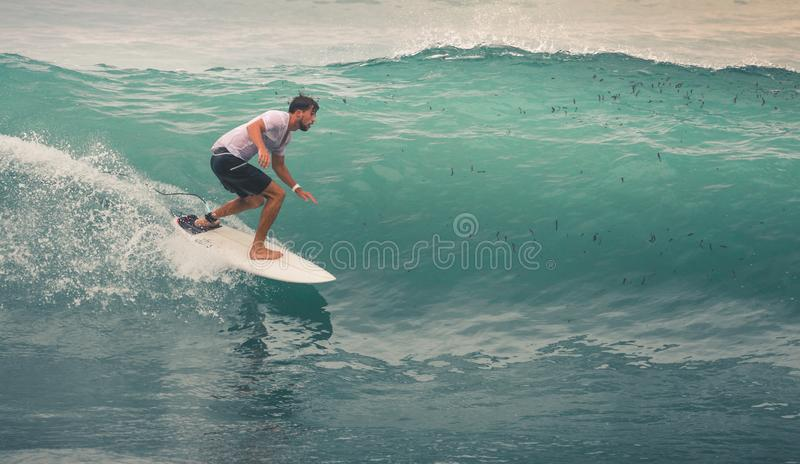 Surfer on Blue Ocean Wave, Bali, Indonesia. Riding in tube. Image of Surfer on Blue Ocean Wave in Bali, Indonesia. Surfer riding in tube. Short surfboard. Deep stock photos