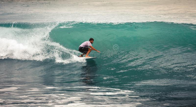 Surfer on Blue Ocean Wave, Bali, Indonesia. Riding in tube. Image of Surfer on Blue Ocean Wave in Bali, Indonesia. Surfer riding in tube. Short surfboard. Deep royalty free stock image