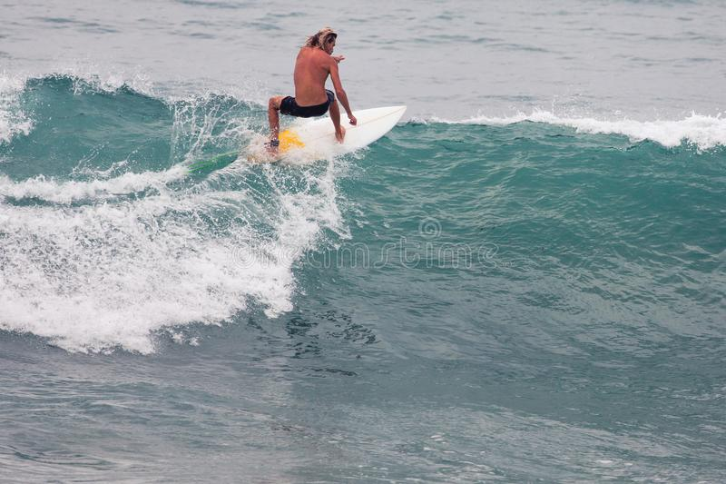 Surfer on Blue Ocean Wave, Bali, Indonesia. Riding in tube. Image of Surfer on Blue Ocean Wave in Bali, Indonesia. Surfer riding in tube. Short surfboard. Deep stock images