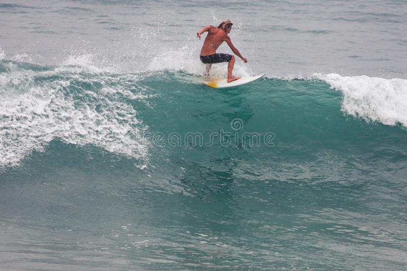 Surfer on Blue Ocean Wave, Bali, Indonesia. Riding in tube. Image of Surfer on Blue Ocean Wave in Bali, Indonesia. Surfer riding in tube. Short surfboard. Deep stock image
